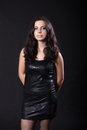 Young woman in a leather black dress posing on dark background Stock Images