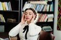 A young woman in the library with closed eyes Royalty Free Stock Photos