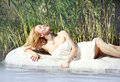 Young woman lies on a white water bed relaxing outdoors background of green plants Stock Photography