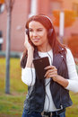 Young woman listening music at autumn outdoor Royalty Free Stock Photo