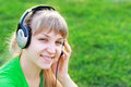 Young woman listening music close up portrait of pretty sitting at the grass Stock Images