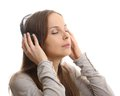 Young woman listening music with headphones on white Stock Images