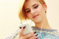 Young woman listening music and texting on her smartphone Royalty Free Stock Photo