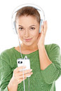 Young woman listening to her music smiling in enjoyment through a set of headphones attached a storage device in hand Royalty Free Stock Images