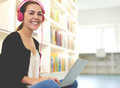 Young woman listening to music as she studies Royalty Free Stock Photo