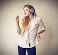 Young woman listening to the music beautiful singing and dancing with headphones Royalty Free Stock Photo
