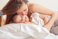 Young woman and litle girl a happy family in bed Royalty Free Stock Photo