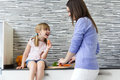 Young woman and little girl eating carrots in the kitchen Royalty Free Stock Photo