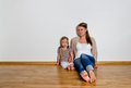 Young woman and little girl sitting on the floor Royalty Free Stock Photography