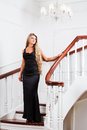 Young woman in a long black dress down the stairs Stock Photography