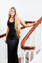 Young woman in a long black dress down the stairs Stock Photos