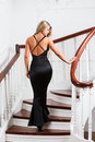 Young woman in a long black dress up the stairs Stock Photography