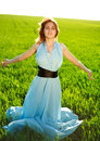 A young woman in a long blue dress enjoying nature the late afternoon sun green field Royalty Free Stock Image