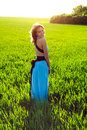 A young woman in a long blue dress enjoying nature the late afternoon sun green field Royalty Free Stock Photography