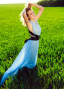 A young woman in a long blue dress enjoying nature the late afternoon sun green field Stock Images