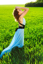 A young woman in a long blue dress enjoying nature the late afternoon sun green field Stock Photo