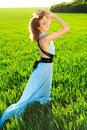 A young woman in a long blue dress enjoying nature the late afternoon sun green field Royalty Free Stock Images