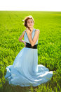 A young woman in a long blue dress enjoying a sunny day the green field Stock Images