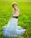 A young woman in a long blue dress enjoying a sunny day the green field Royalty Free Stock Photos