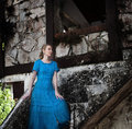 The young woman in a long blue dress stands near the old destroyed stone wall of the building Royalty Free Stock Photos