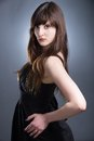 Young woman with long brown hairs in black dress Royalty Free Stock Image