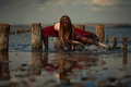 Young woman in long dress is dancing in water on sea background. Royalty Free Stock Photo