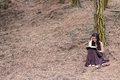 Young woman in long dress reads a book sitting under a tree Royalty Free Stock Photo