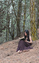 Young woman in long dress sits under a tree with book Royalty Free Stock Photo