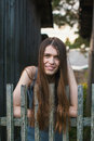 Young woman with long hair standing near the wooden fence in the village. Royalty Free Stock Photo