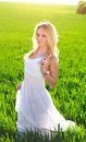 A young woman in a long white dress enjoying nature the late afternoon sun green field Royalty Free Stock Images