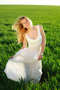 A young woman in a long white dress enjoying nature the late afternoon sun green field Royalty Free Stock Photo