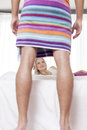 Young woman looking at man wrapped in towel at hotel room women men Royalty Free Stock Photography