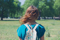 Young woman looking at meadow a is standing in a park on a summer day and is waiting for the flowers in a to grow Royalty Free Stock Images
