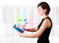 Young woman looking at modern tablet with colourful technology i business icons Stock Images