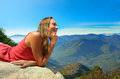 Young woman looking at the mountains on the edge of a cliff Stock Image
