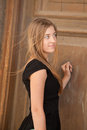 Young woman looking at an old door a about to open staring straight the camera Royalty Free Stock Photo