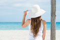 Young woman looking at sea rear view of a girl wearing white hat Stock Photo