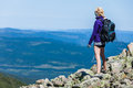 Young woman looking at the view from the top of the hill with backpack Stock Images