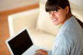 Young woman looking at you while working on laptop Royalty Free Stock Photos