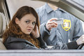 Young woman looks away after being pulled over by police off in the distance a officer horizontal Royalty Free Stock Photography