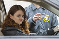 Young woman looks away after being pulled over by police off in the distance a officer horizontal Stock Photography