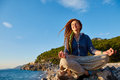Young woman in the lotus position with dreadlocks sitting on cliff against sea and blue sky at early morning Royalty Free Stock Photography