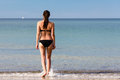Young woman with a lovely figure entering the sea wearing black bikini her long brown hair tied in ponytail walking away from Royalty Free Stock Image