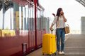Young woman with luggage talking by cellphone at a Royalty Free Stock Photo