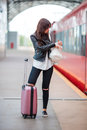 Young woman with luggage talking by cellphone at a train station. Caucasiam tourist waiting her express train while her Royalty Free Stock Photo