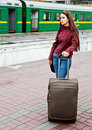 Young woman with luggage is waiting a train Royalty Free Stock Image