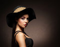 A young woman in luxurious clothes and a hat attractive lady over the retro background Stock Image
