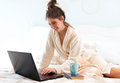 Young woman lying on the bed, using a laptop Royalty Free Stock Photo