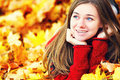 Young woman lying down in autumn leaves smiling Stock Image