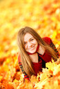 Young woman lying down in autumn leaves smiling Stock Photos
